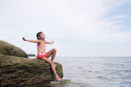 Young girl enjoying a peaceful day by the sea. photo