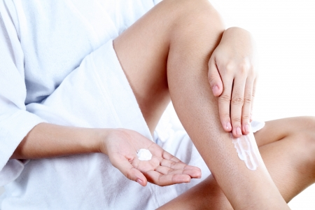 Lady applying lotion on a leg Close up  photo
