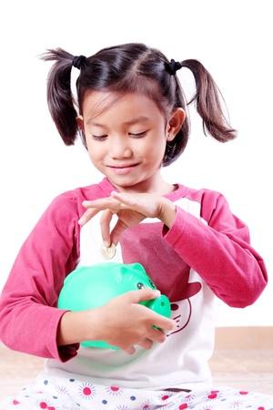 Young girl saving a coin in a piggy bank. photo