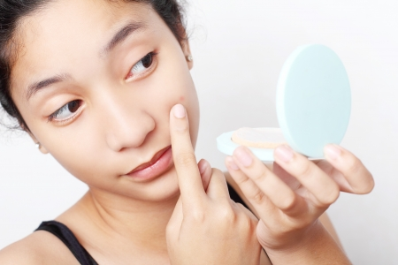 Teenager checking her face for pimple in the mirror. 版權商用圖片