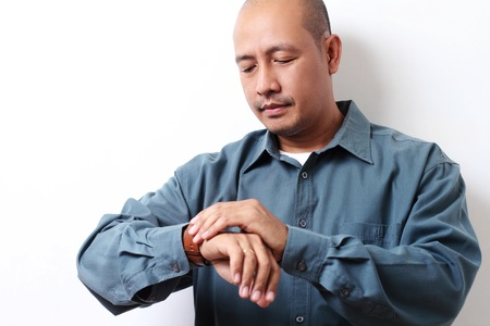 Bored asian man looking at his wrist watch.