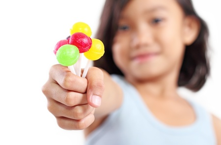 close up food: Young girl showing a sweet and colorful lollipops.
