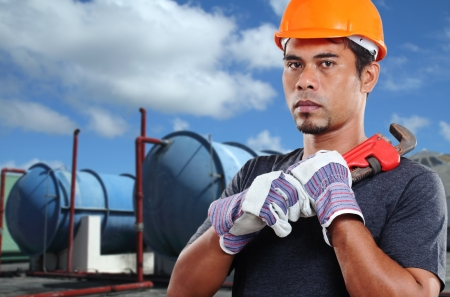 Mature asian worker with a wrench. photo