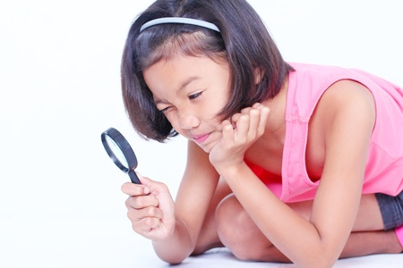 Young girl looking into a magnifying glass. Stock Photo - 18202549