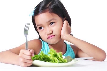 ni�os tristes: Retrato de una chica joven que no les gusta comer verduras. Foto de archivo