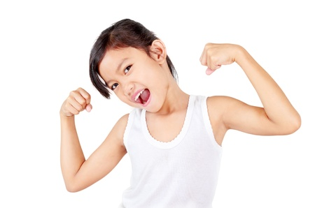 kids exercise: Young healthy girl flexing her muscles.Isolated in white background. Stock Photo