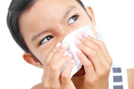 toser: Retrato de una joven chica estornudos en un pañuelo de papel.