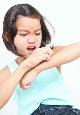 itchy: Portrait of a young asian girl scratching her arm. Stock Photo