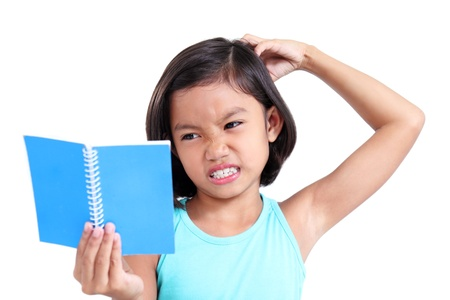 scratching head: Portrait of a young asian girl scratching her head while having difficulty reading.