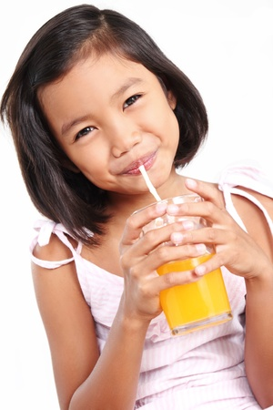 Happy asian girl drinking an orange juice. 版權商用圖片