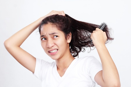 Young asian lady with an unpleasant facial expression while brushing her curly hair. 版權商用圖片