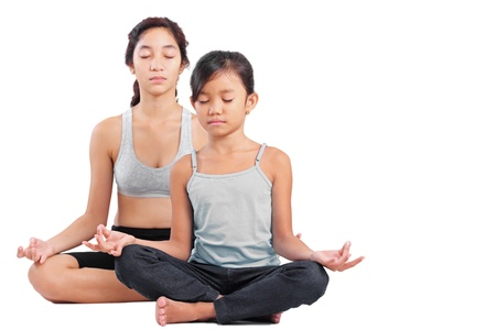 Young girl and a lady in yoga meditation position. photo