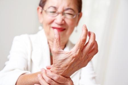 artritis: Mujer mayor con artritis de la mano mueca de dolor. Foto de archivo