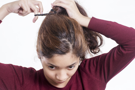 frizzy: Young lady fixing a messy frizzy hair.