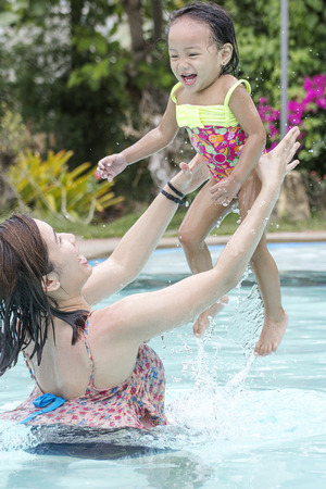 Woman tossing a little girl in the air. Fun in the swimming pool. photo