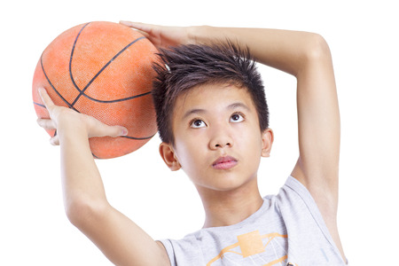 Young basketball player concentrating in shooting the ball.Isolated in white background. photo
