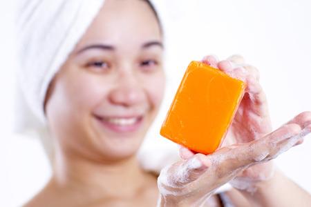 productos de aseo: Señora asiática que muestra una barra de jabón de naranja. Foto de archivo