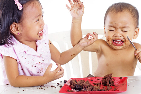 messy kids: Messy kids quarreling over a plate of cake.