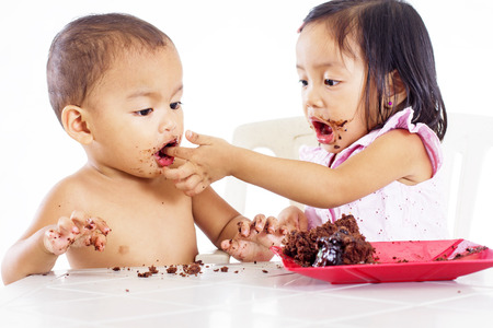 Young little girl feeding a little boy with a cake with her finger. 版權商用圖片