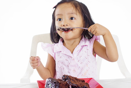 young asian girl eating a chocolate cake with a fork.