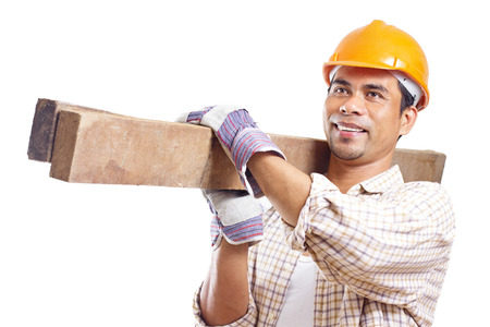 Portrait of a smiling construction worker carrying pieces of lumber. Isolated in white background. photo