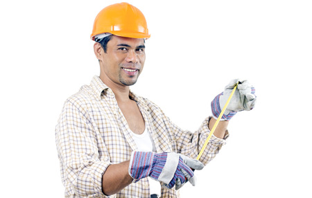 Smiling construction worker holding a measuring tape.Isolated in white background. photo