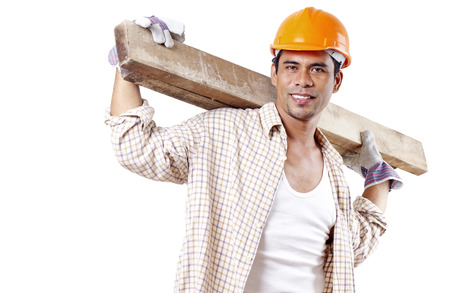 Portrait of a smiling carpenter carrying lumber in his shoulder. photo