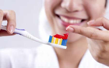 pasta dental: Cierre de vista de las manos con el cepillo de dientes y pasta de dientes. Foto de archivo