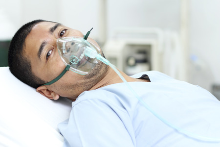 the patient: Adult male patient in the hospital with oxygen mask. Stock Photo