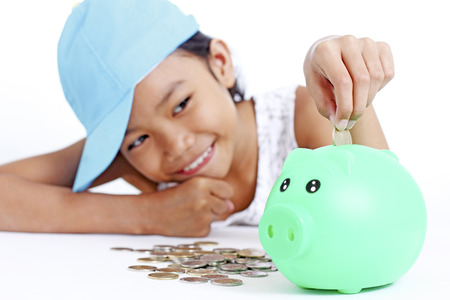 Happy young asian girl saving a coin in a piggy bank. Isolated in white background. 版權商用圖片
