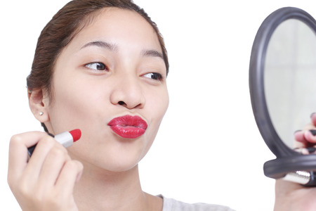 red lip: Beautiful lady checking her lips with lipstick in a mirror. Isolated in white background. Stock Photo