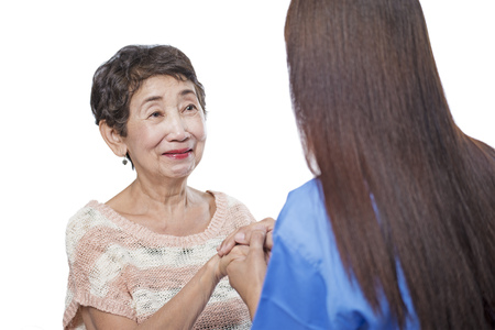 Health worker comforting an elderly patient. Isolated in white background. photo