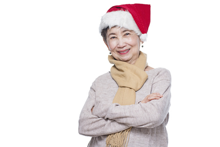 Portrait of a smiling senior lady wearing a Santa hat. Isolated in white background. photo
