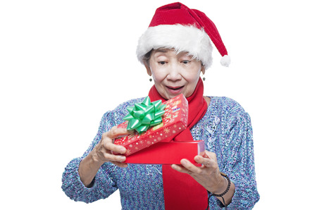 Senior lady receiving a surprise christmas gift. Isolated in white background. photo
