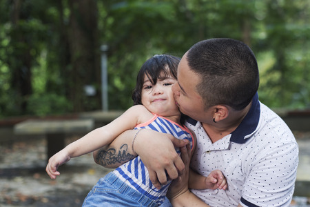 Close up view of a father lovingly kissing her young daughter. outdoor shot with blurred trees at the background.
