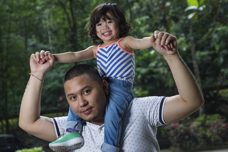 Young father carrying daughter in his shoulder. Close up. Forest with grown up trees at the background. Stock Photo
