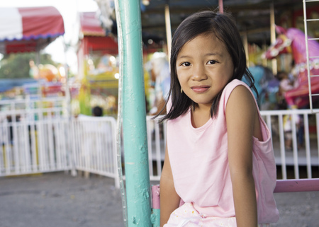 Portrait of a young girl sitting in the amusement park. Carousel at the background.