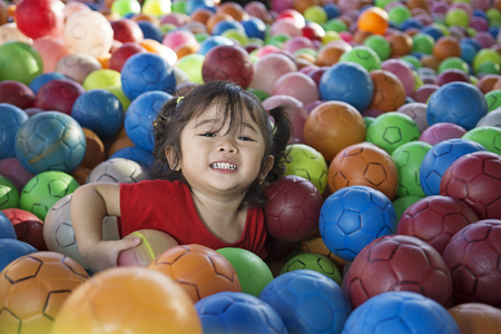 Little girl enjoying playing with lots of balls.