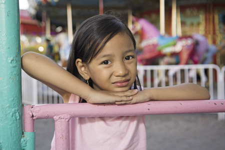 Portrait of a lonely girl at an amusement partk. Carousel at the background. 版權商用圖片