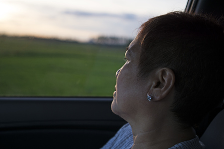 Mature woman watching sunset from inside a car window. Ricefield at the background. 版權商用圖片