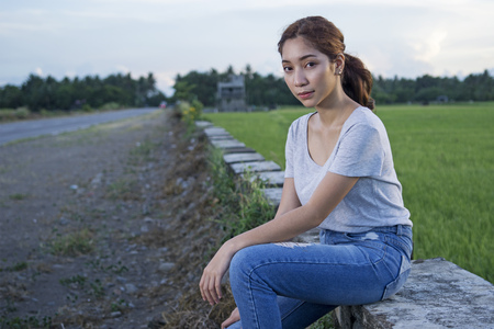 Outdoor portrait of a young beautiful lady by the roadside. Ricefield at the background.
