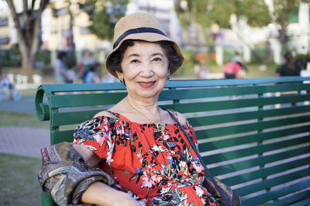 Happy old woman sitting and relaxing at a park bench. 版權商用圖片