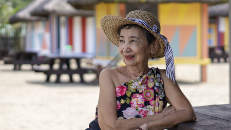Smiling happy old woman leaning on a table enjoying an outdoor tropical view. 版權商用圖片