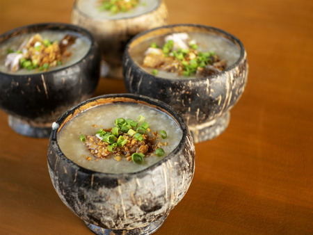 Hot porridge served in an improvised coconut shell bowl garnished with green onion and toaste garlic.