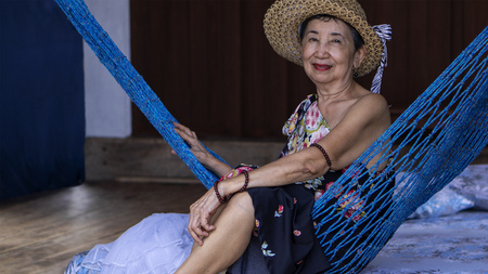 Smiling happy old asian woman sitting on a hammock inside a cottage.