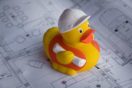 Rubber toy duck construction worker sitting on building plan. Easy building and construction concept. Safety, protection and planning