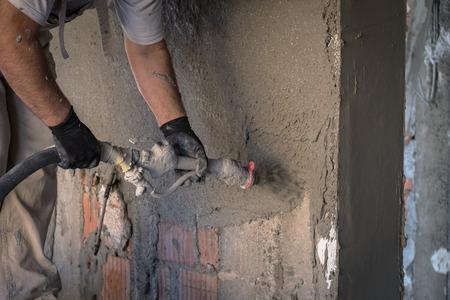 左官工事機械と壁の表面にセメント石膏を適用する建設労働者