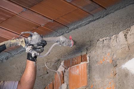 石膏マシンで壁面にセメント石膏を適用する建設作業員