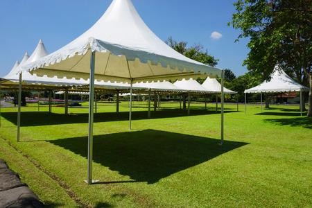 weißes Zelt mit grünem Gras im Gartenpark mit Schuppen - Foto Indonesien in