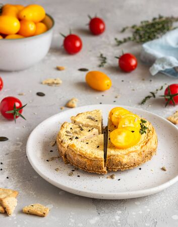 Savory cheesecake with tomatoes and thyme. Copy space. Light gray background. Reklamní fotografie
